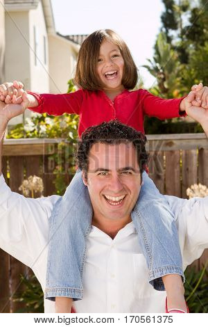 Portrait of a happy Hispanic father hugging his daughter.