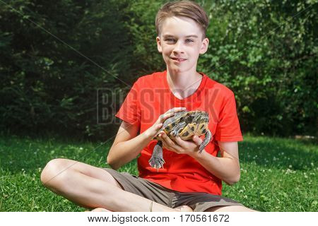 Cute teenager boy wearing red t-shirt sitting on a lawn in a summer garden holding turtle looking at camera smiling