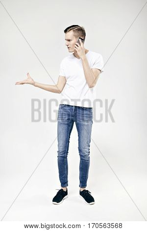 Handsome hipster guy full-length standing talking by phone and swears isolated on white background wearing jeans and t-shirt