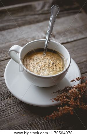 Chill and Relax with Hot Coffee and Dry Flower on old wooden in vintage color tone used for food ad or website promote. beverage for people to work place