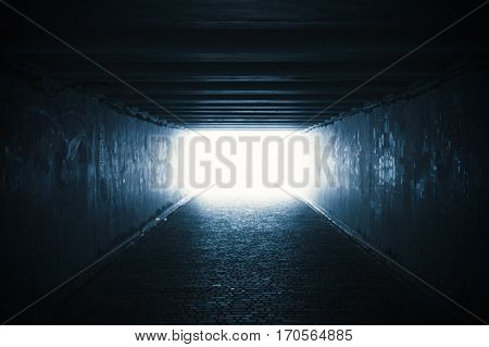Empty dark underpass tunnel with light in the end, soft focus