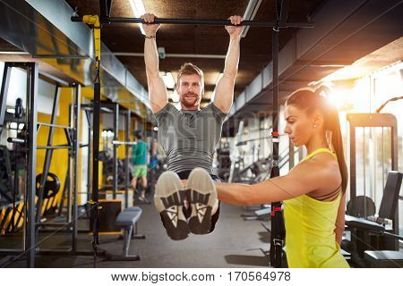 Male doing pull-up exercise with coach assisting in fitness club