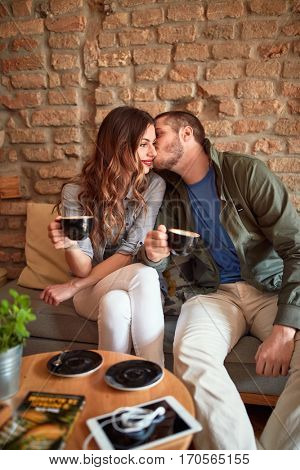 Amorous couple kissing in cafe and enjoying in coffee
