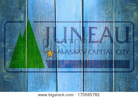 Vintage Juneau flag on grunge wooden panel