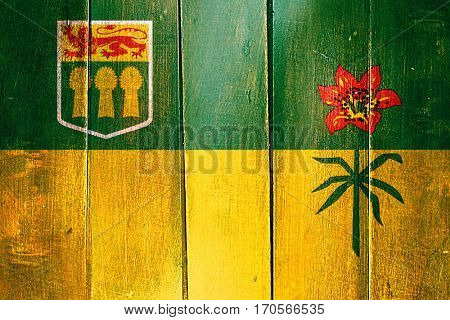 Vintage Saskatchewan flag on grunge wooden panel