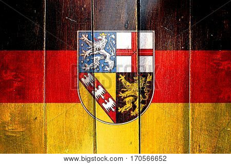 Vintage Saarland flag on grunge wooden panel