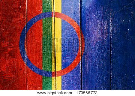 Vintage Sami people flag on grunge wooden panel