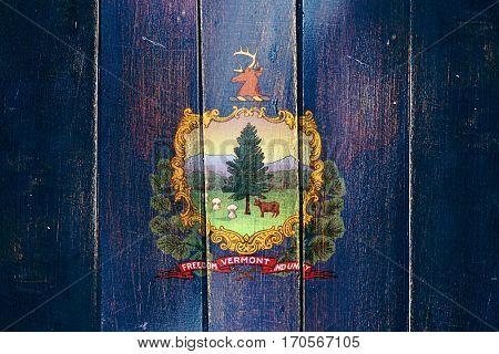 Vintage vermont flag on grunge wooden panel