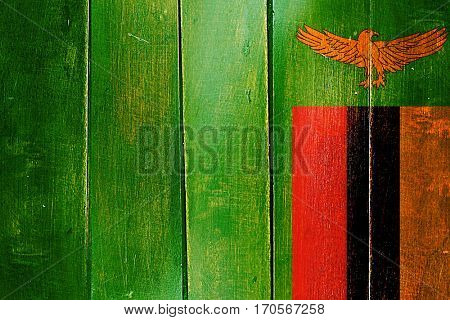 Vintage Zambia  flag on grunge wooden panel
