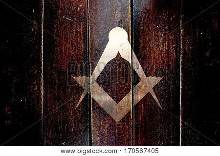 Vintage freemason symbol on a grunge wooden panel