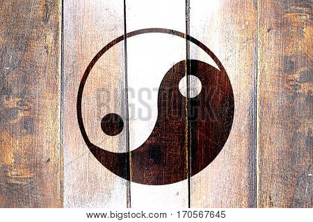 Vintage yin yang symbol on a grunge wooden panel