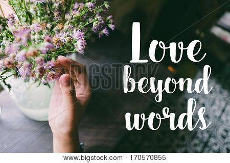 Life quote. Motivation quote on soft background. The hand touching purple flowers. Love beyond words.