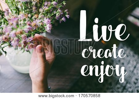 Life quote. Motivation quote on soft background. The hand touching purple flowers. Live create enjoy