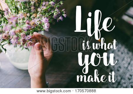Life quote. Motivation quote on soft background. The hand touching purple flowers. Life is what you make it.