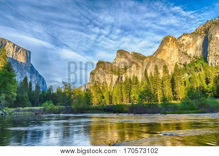 Granite cliffs reflecting in Merced river during dusk, Yosemite National Park. California, USA