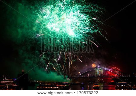 Green fireworks with boats parade at Harbour Bridge in Sydney bay at midnight for the new years eve 2015, shot from a boat.