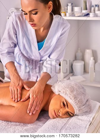 Massage woman therapist making manual therapy back. Hands of masseuse close up. Treatment of spinal injuries 40 old client in spa salon. Young beautician on foreground.