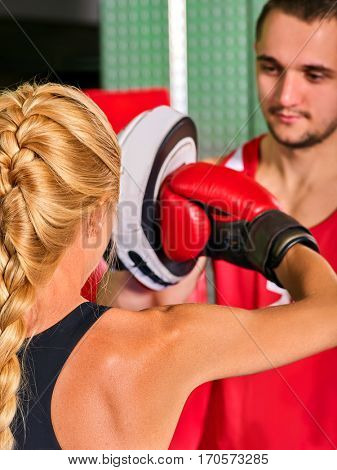 Boxing workout woman in fitness class. Sport box exercise two people. Man trainer holding sport mitts in gym. Female boxing gloves are red. Close up of female back.