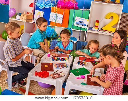 Child dough play in school. Plasticine for children. mold from plasticine in kindergarten .Kids knead modeling clay with hands in preschool.