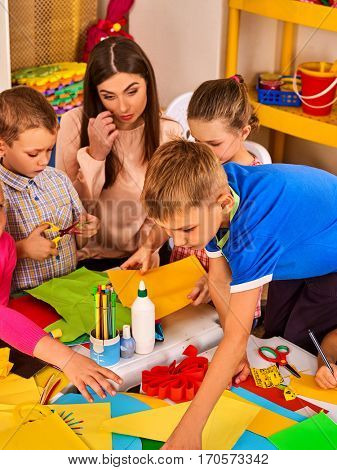 Children cutting paper in class. Kids development and social lerning children in school. Children's project in kindergarten. Pictures into background. Girl and boy with teacher together.