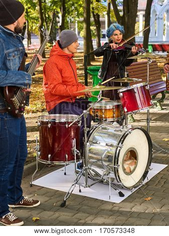 Festival music band. Friends playing on percussion instruments in city park. Girl with blue hair. Fountain and trees in the background.