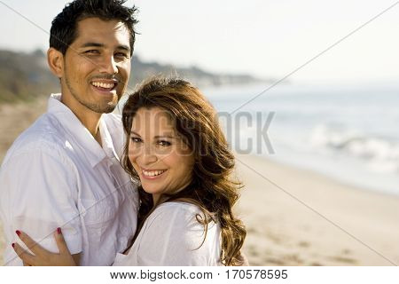 Portrait of a beautiful Hispanic couple laughing and smiling.
