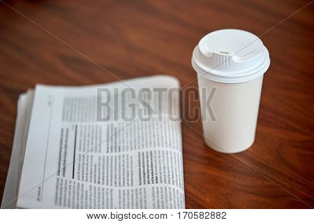 break, mass media and news concept - coffee drink in paper cup and newspaper on table