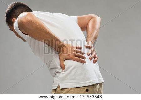 people, healthcare and problem concept - close up of man suffering from pain in back or reins over gray background