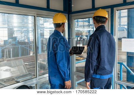 Rear view of two workers wearing yellow hard hats while using a tablet PC in the interior of a modern factory