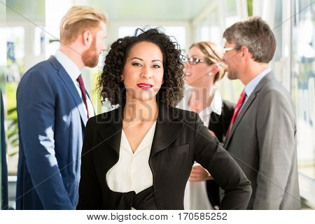Businesswoman standing with hand on her hip, with her co-workers talking in the background