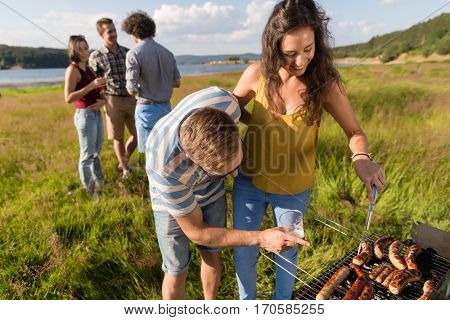 Young man and woman grilling sausages on barbecue grill at party in nature