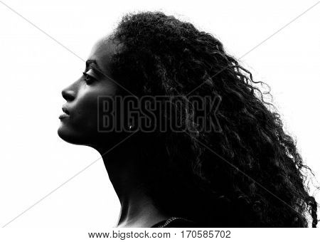 Greyscale head shot portrait in profile of a beautiful proud young woman with gorgeous curly black hair raising her head and stretching her neck over a white background