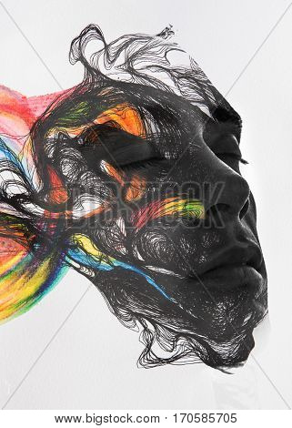 Attractive man's portrait fading and flowing into lines and colorful brushstrokes