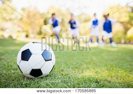 Extreme close up view of soccer balloon against children background in park