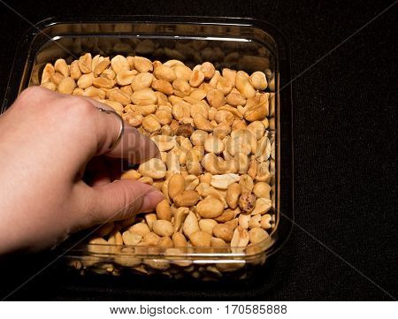 Hand is picking up salted peanuts on black background.