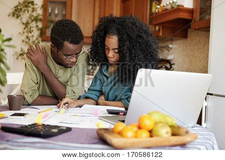 Stressed Young Dark-skinned Married Couple Looking Frustrated While Calculating Domestic Budget Toge