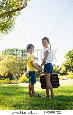 Children holding their hands looking back while holding a luggage in a park