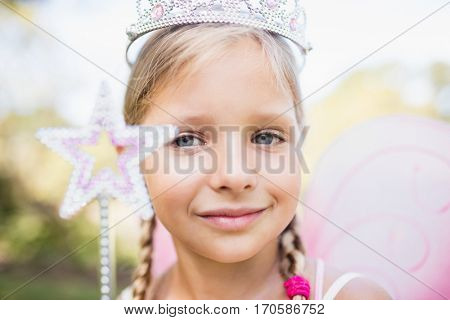 Portrait of adorable girl pretending to be a princess in the park