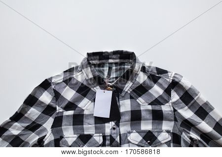 clothes, fashion and objects concept - close up of checkered shirt with price tag on white background