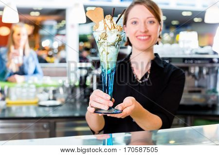 Saleswoman in ice cream parlor presenting sundae