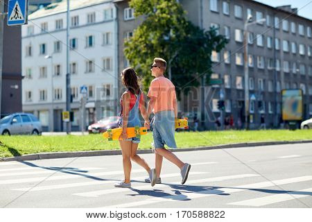 summer, relations, traffic, extreme sport and people concept - happy teenage couple with short modern cruiser skateboards crossing city crosswalk