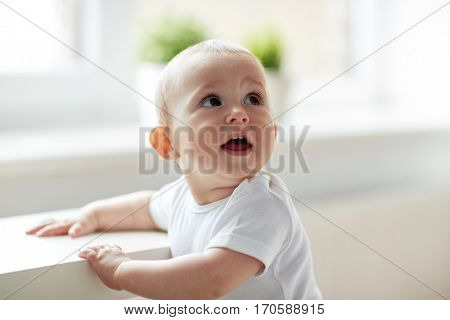childhood, babyhood, emotions and people concept - close up of happy little baby boy or girl at home
