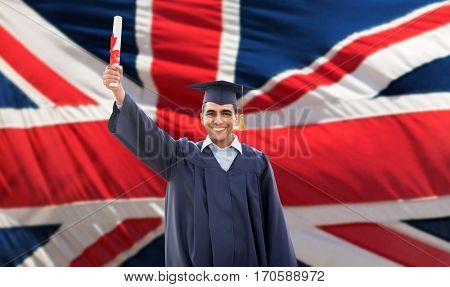 education, graduation and people concept - happy male student in mortarboard and bachelor gown with diploma over british flag background