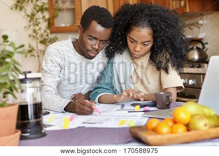 Serious Young African Male In Glasses Holding Felt Pen, Calculating Domestic Expenses While Managing