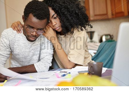 African Couple Is Bankrupt. Sad Male In Glasses Holding Piece Of Paper Feeling Effortless To Do Some