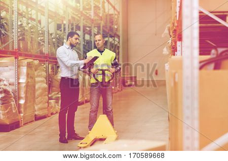 wholesale, logistic, people and export concept - manual worker and businessmen with loader and clipboard at warehouse