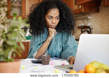 Beautiful African Woman Sitting In Front Of Laptop Computer, Looking At Screen With Serious And Conc