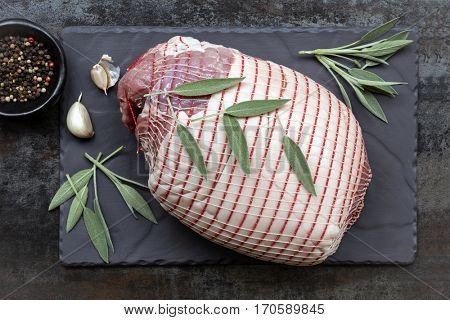 Raw pork roast, top view on slate, with sage leaves, garlic and black peppercorns.