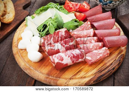 Charcuterie board with italian cured meat, cheese and rocket salad