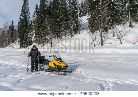 the fisherman stands with ice screws near the snowmobile